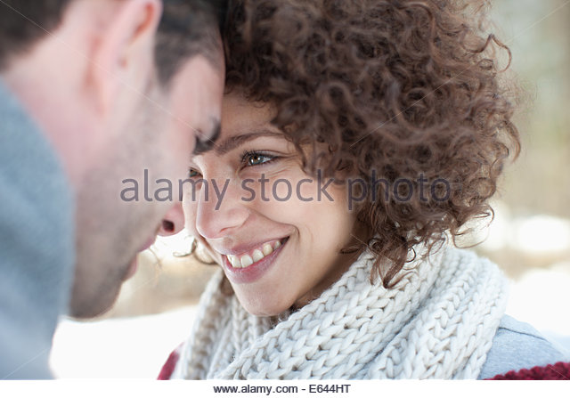 Man and woman smiling at one another - Stock Image