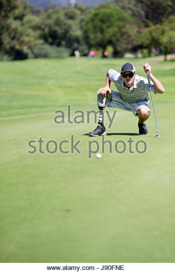 Male Golfer With Artificial Leg On Course Lining Up Ball On Green - Stock-Bilder