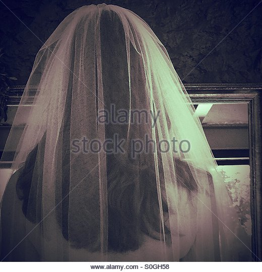 Bride looking in the mirror - Stock Image