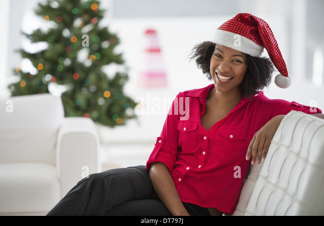 A woman wearing a red and white Father Christmas hat. Sitting on a sofa. Decorated tree. - Stock Image