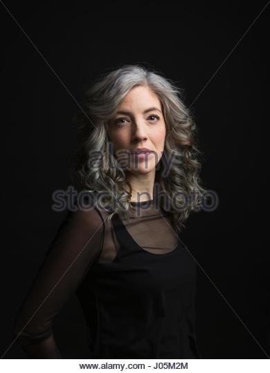 Portrait serious, confident woman against black background - Stock Image
