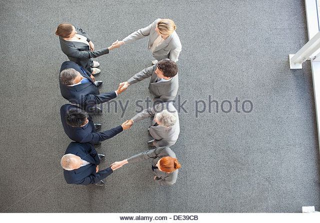 High angle view of business people shaking hands in a row - Stock Image