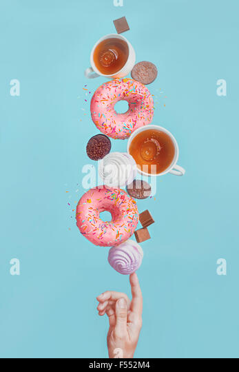 Balancing donuts.Glazed donuts, tea cups, marshmallows and chocolate chips, balancing on the tip of one's finger - Stock Image