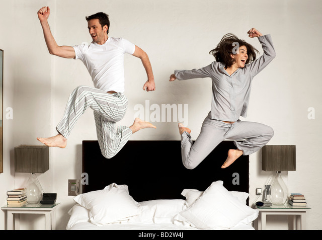 couple leaping out of bed - Stock Image