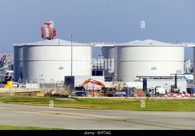 Aviation fuel tanks at London Heathrow Airport. Airport radar visible in background. - Stock Image