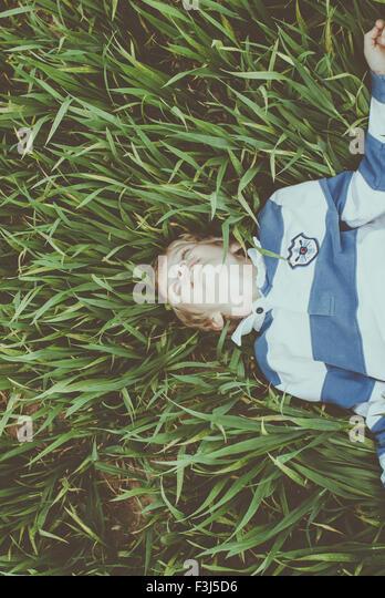 Cute little boy lying in long grass smiling - Stock Image