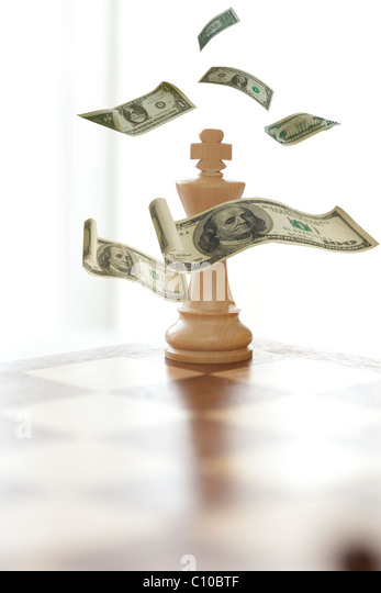 king in chess game stands alone with money floating down. - Stock Image