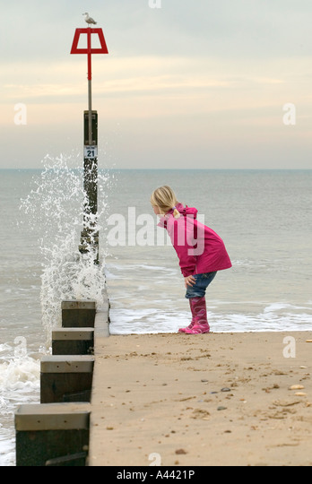 Young girl watching as the waves crash against the tide wall - Stock-Bilder