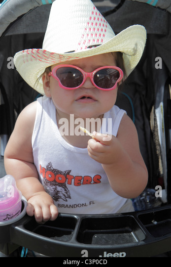 Florida Plant City Florida Strawberry Festival annual event girl straw hat stroller toddler - Stock Image