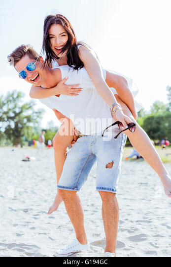 Playful couple enjoying their summer vacation as the man carries the woman piggyback - Stock Image