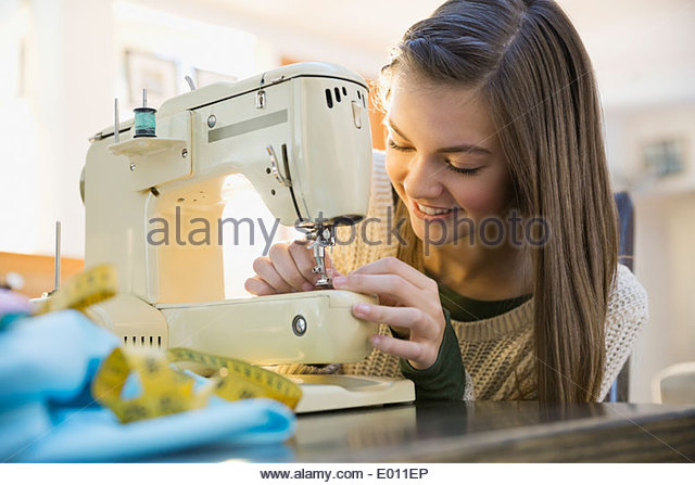 Girl using sewing machine - Stock Image