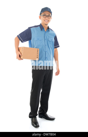 Delivery person delivering package smiling happy in blue uniform. Handsome Asian man courier full length isolated - Stock Image