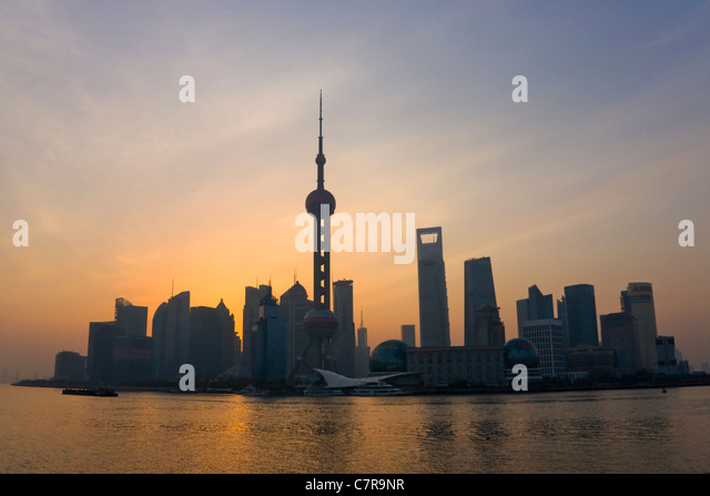 Pudong skyline dominated by Oriental Pearl TV Tower at sunrise by Huangpu River, Shanghai, China - Stock Image
