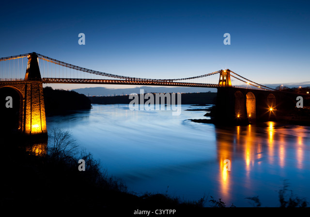 Evening illuminations on the Menai Bridge spanning the Menai Strait, Anglesey, North Wales, UK. Spring (April) 2011. - Stock-Bilder