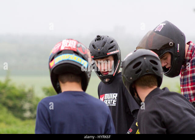 Five young helmeted skateboarders before a downhill race - Stock Image
