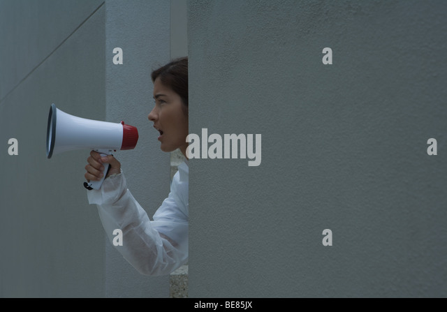 Woman in protective suit shouting into megaphone, side view - Stock Image