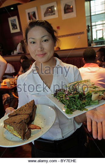 Baltimore Maryland East Pratt Street Miss Shirley's Cafe restaurant business Asian woman waitress plate food - Stock Image