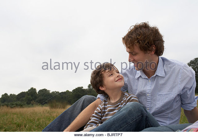Father and son sitting in a field - Stock Image