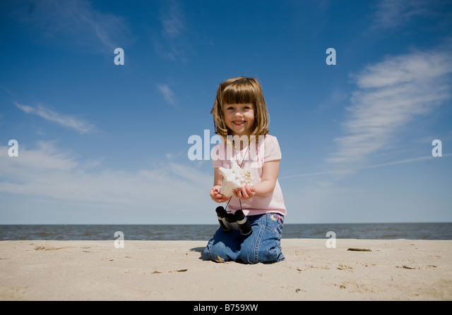 Four year old girl shows shell at the beach, Grand Beach Provincial Park, Manitoba, Canada - Stock Image