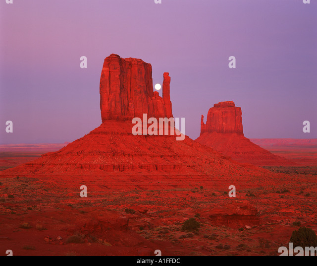 The moon above the rock formations known as The Mittens in the Navajo Reservation in Monument Valley Utah USA G - Stock Image