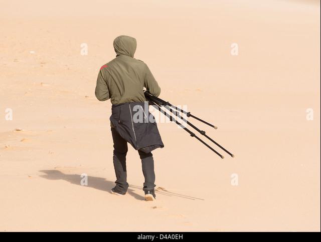 Man holding a tripod. - Stock Image