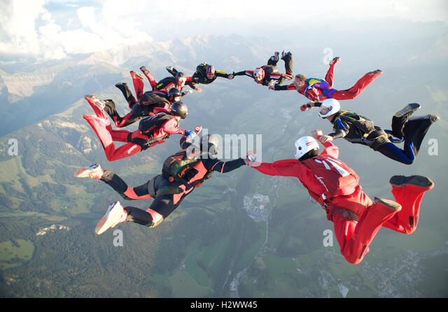 Nine skydivers form a star formation over Gruyères in Switzerland - Stock Image