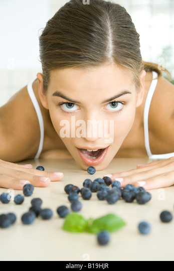 Fresh blueberries scattered across counter, young woman opening mouth to eat one - Stock-Bilder