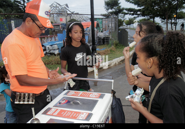 Panama City Panama Amador Panama Canal street vendor ice cream bar popsicle frozen treat snack Hispanic man girl - Stock Image