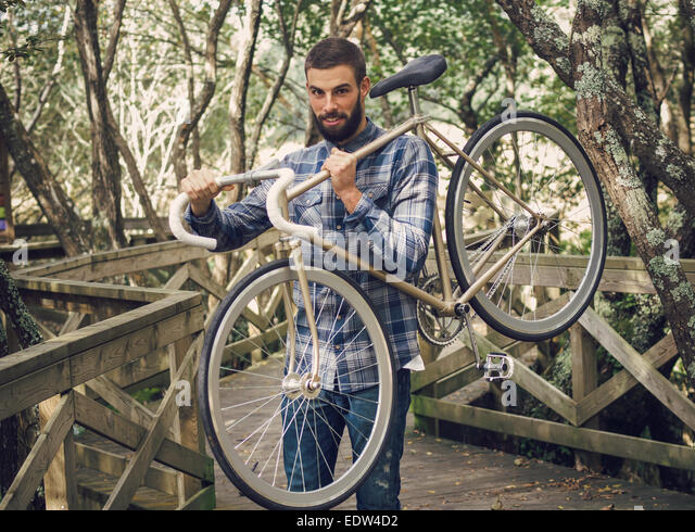 Hipster man holding his bicycle in a park outdoors - Stock-Bilder