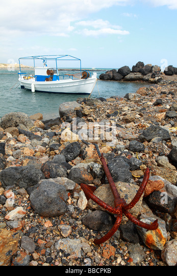 A small Greek fishing boat or caique firmly anchored to a breakwater in southern Crete Greece - Stock Image