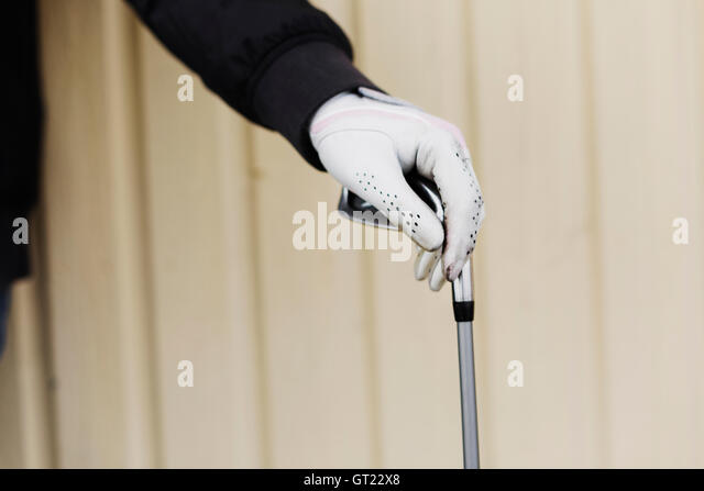 Cropped image of woman's hand holding golf club against wall - Stock-Bilder