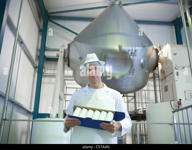 Worker holding goat's butter in dairy - Stock Image