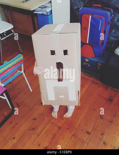 Dressing up toddler in cardboard box. - Stock Image