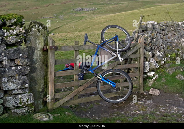 Cyclist and cycle at a staged accident over a fence during Mountain Bike trip in Yorkshire Dales, Great Britain - Stock Image