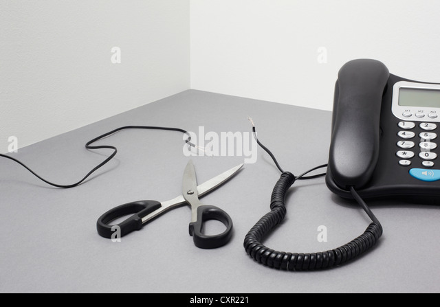 Landline phone, cut cable and scissors - Stock Image