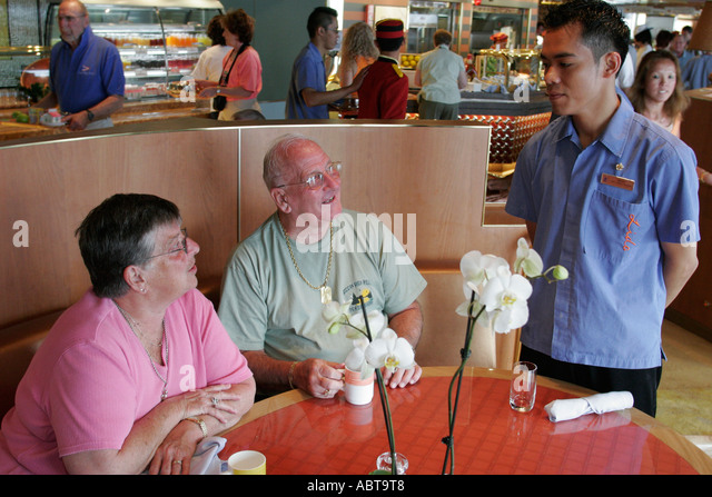 BVI Tortola Holland America Caribbean cruise from New York ms Noordam Lido Restaurant couple Asian male waiter - Stock Image