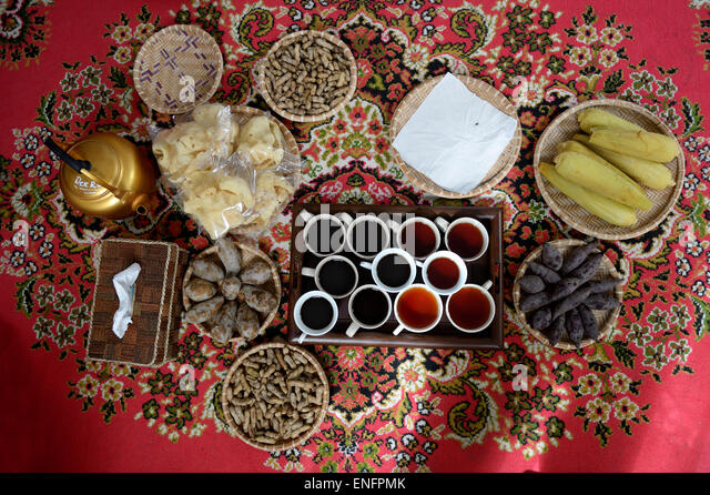 Local food, tea and coffee on a red carpet, Gampong Nusa, Aceh, Indonesia - Stock Image