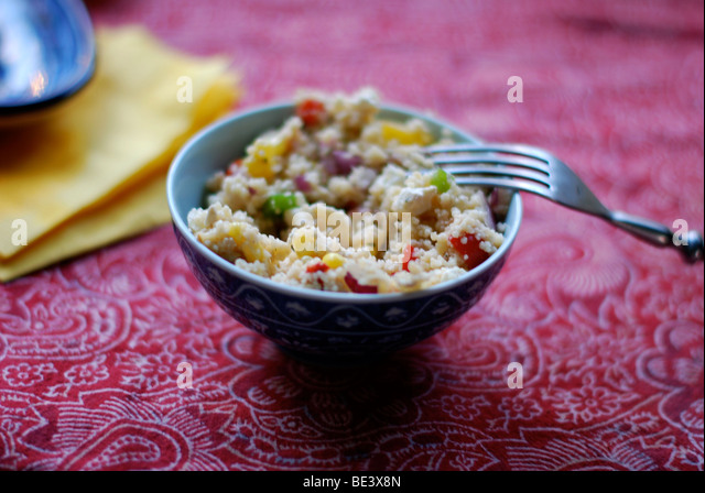 Couscous in blue bowl on red table cloth - Stock-Bilder