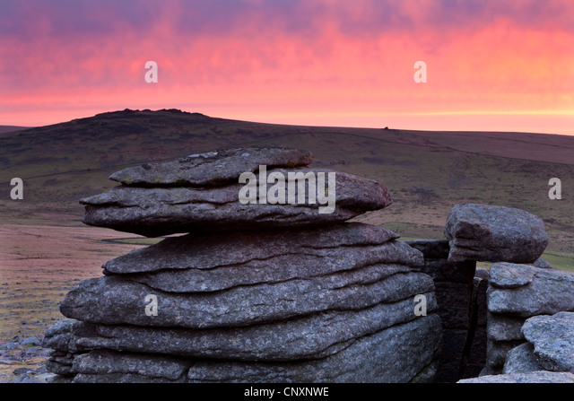 Colourful dawn sky above Great Mis Tor, viewed from the granite outcrops of Great Staple Tor, Dartmoor, Devon, England. - Stock Image