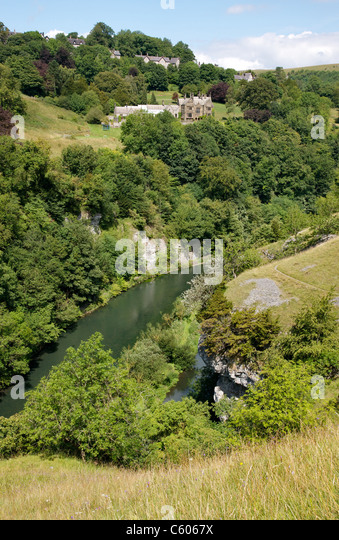 Looking across the River Wye and Water cum Jolly Dale to Cressbrook Hall and village in the Derbyshire Peak District - Stock Image