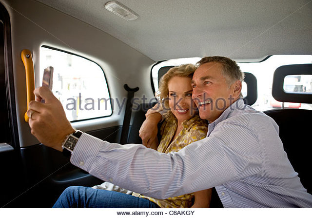 A middle-aged couple in a London taxi, taking a photograph of themselves - Stock Image