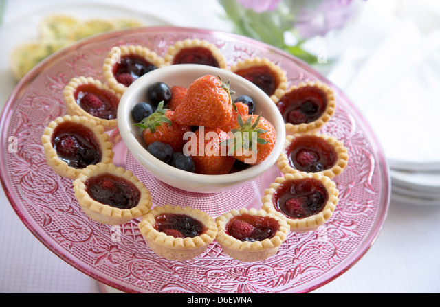 Mini sweet pastry summer berry jam tarts, with extra fresh berries. - Stock Image