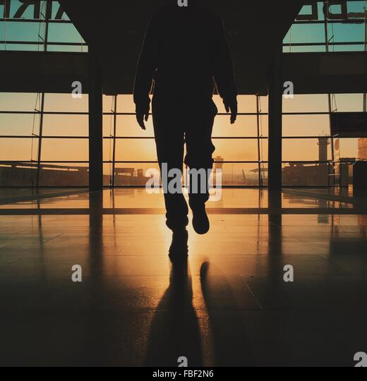 Low Section Of Silhouette Man Walking At Airport - Stock Image