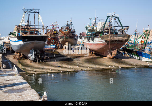 Essaouira, Morocco.  Fishing Boats on Dry Dock Undergoing Maintenance. - Stock Image
