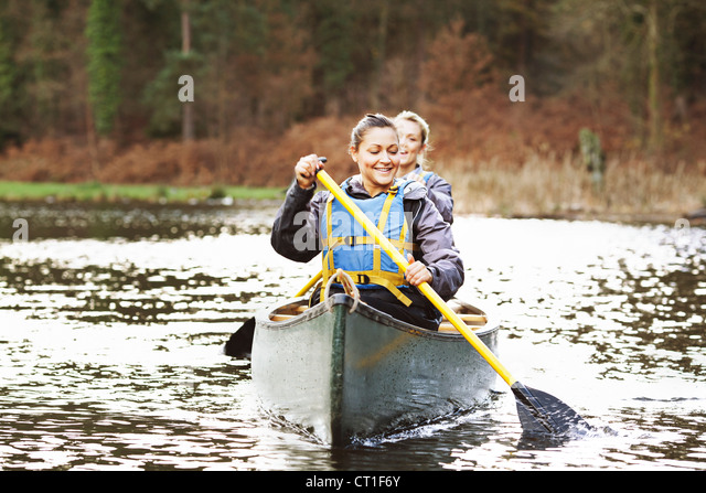 Women rowing canoe on still lake - Stock Image