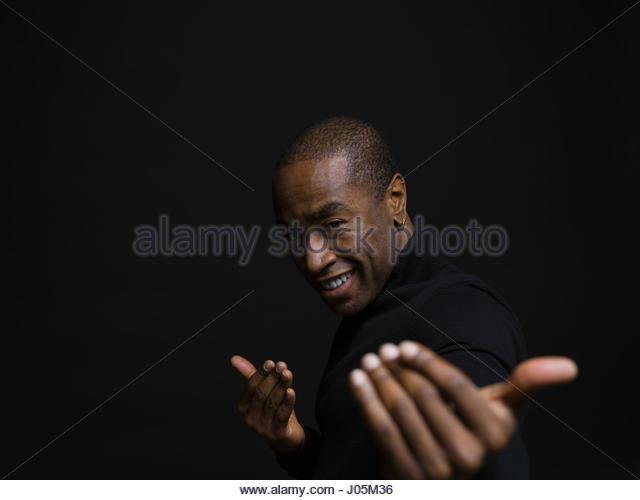 Portrait playful African American man gesturing against black background - Stock Image