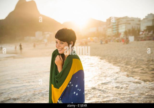 Young woman wrapped in Brazilian flag, Ipanema beach, Rio, Brazil - Stock-Bilder