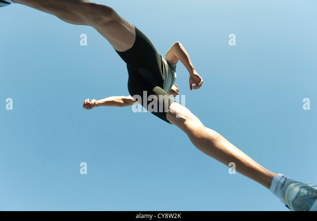 Man jumping in air, directly below - Stock Image