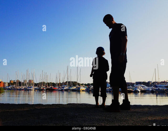 Stockholm, Sweden A Boy And His Father Throwing Rocks Into The Water And Look At Boats - Stock Image