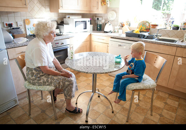 Grandmother sitting at the table with her grandson (aged 3) while he drinks a cup of milk and eats a biscuit, United - Stock-Bilder